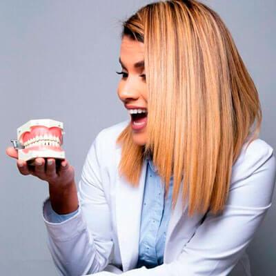 Dr. Odelsis Barrero smiling at a sample of denture